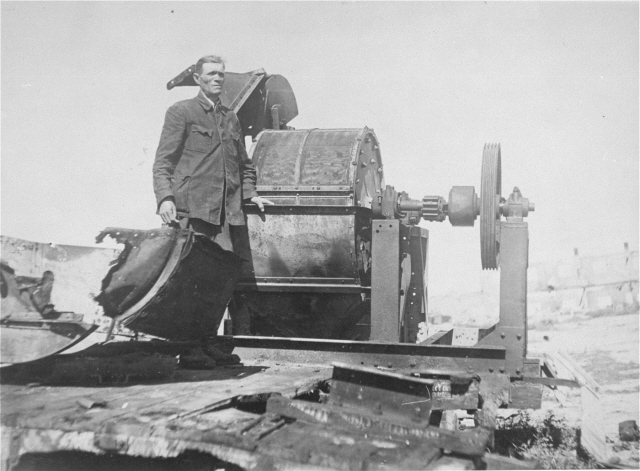 Moses Korn poses next to bone crushing machine