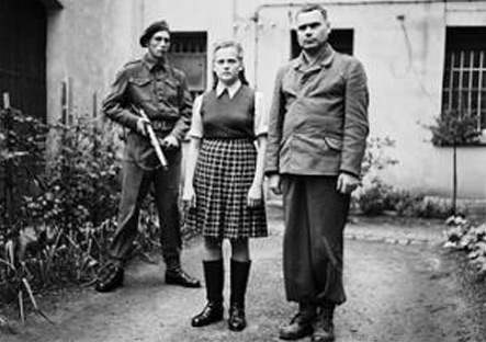 Irma Grese and Josef Kramer standing in the courtyard